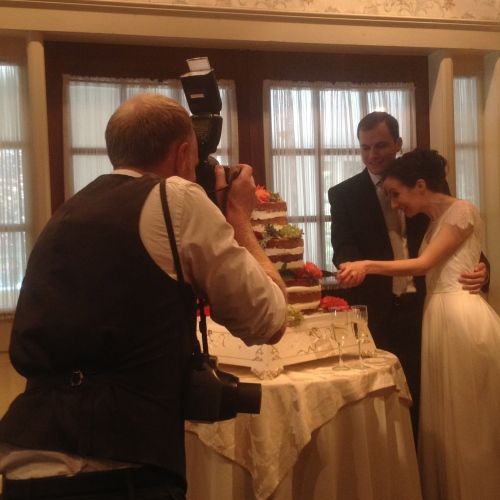 wedding photographer takes a photograph of bride and groom cutting the cake