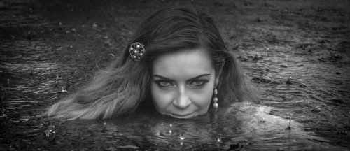 My favorite image of the series, rain droplets falling on the surface of the pool and those piercing eyes and mysterious smile.