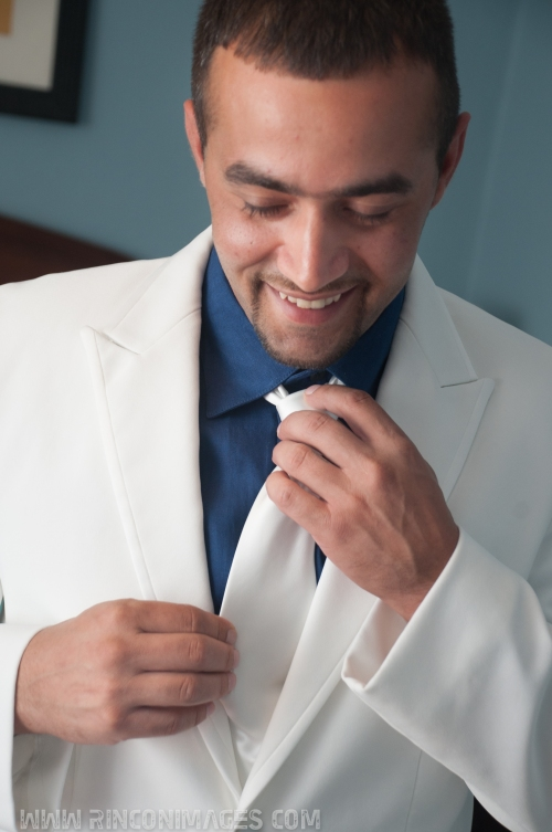 Groom wearing a white suit and navy blue shirt fixing his white tie before the wedding. -Wedding photographer puerto rico