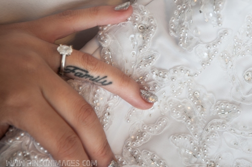 "Detail photograph of a brides hand with a tattoo that says ""Family"" on her ring finger. Her ring finger also has a solitaire diamond engagement ring on it. Her hand is resting on her beaded white wedding dress. Wedding photographer puerto rico."