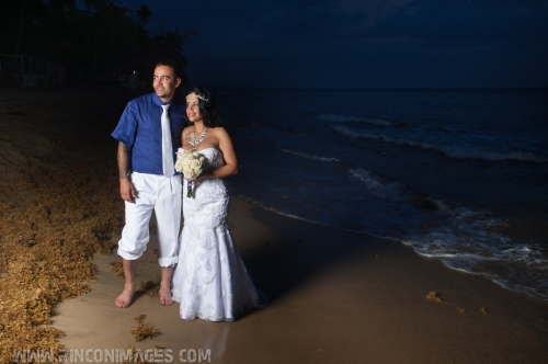 Bride and groom are barefoot on the beach. She is wearing a white wedding dress and holding a bouquet of white flowers. he is wearing a navy shirt with a white suit. wedding photographer puerto rico