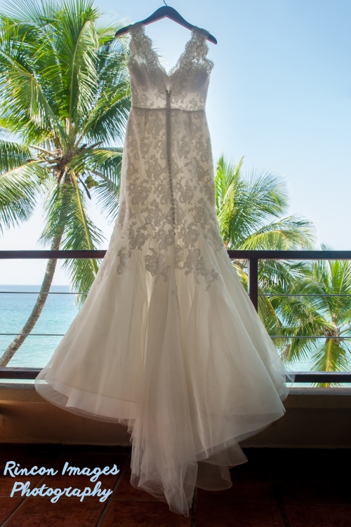 White wedding dress hanging outside with palm trees in the background. wedding photographer rincon puerto rico