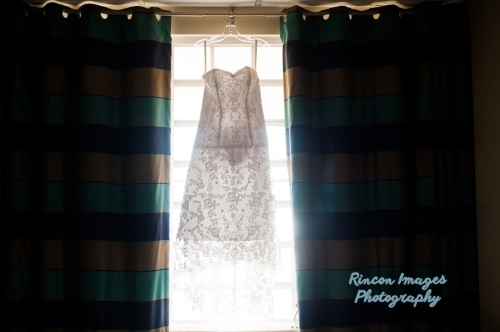 White wedding dress with beautiful beading hanging in a window. Photographed by Rincon Images wedding photographer Rincon Puerto Rico.