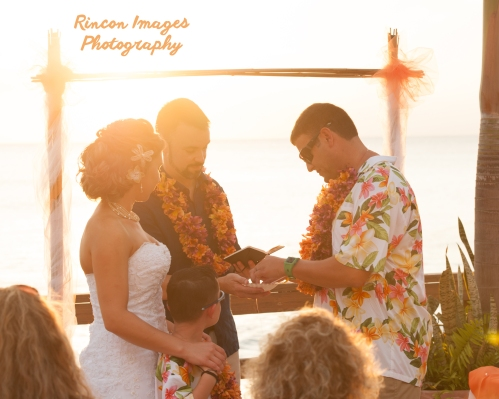Scott slipping the wedding ring onto Colleens finger and the sun sets during their wedding by the beach in Rincon, Puerto Rico. Wedding photography by Rincon Images wedding photography. Wedding photographer in Rincon Puerto Rico.