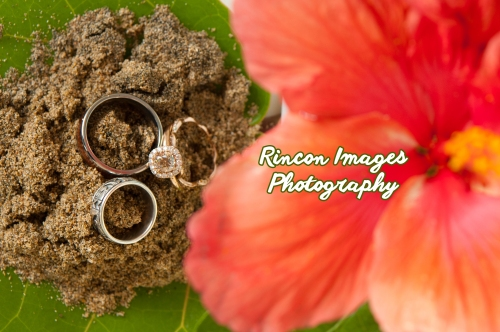 Three wedding rings sitting in sand with a tropical hibiscus flower. Photograph by Rincon Images photography, wedding photographer Rincon Puerto Rico.