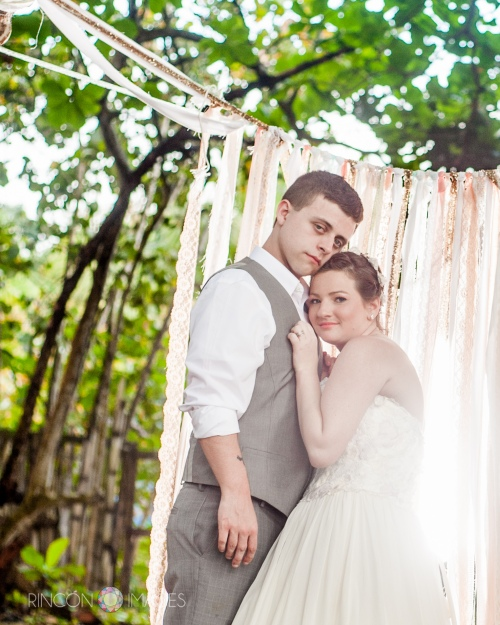 The bride and her groom in front of their DIY wedding ceremony backdrop in Rincon, Puerto Rico.