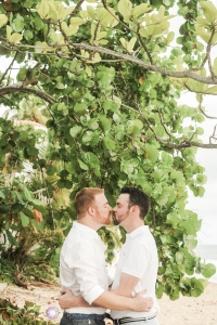 The happy couple kissing in front of the sea grape leaves, on the beach in Rincon Puerto Rico. LGBT wedding photographer Puerto Rico