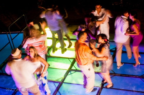 Guests having fun on the light up dance floor covering the outdoor pool just after the cake was cut.